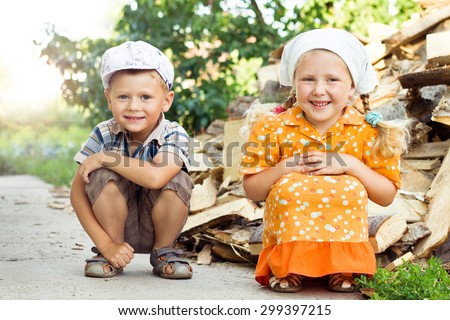 Russian laughing boy and girl at firewood  - stock photo