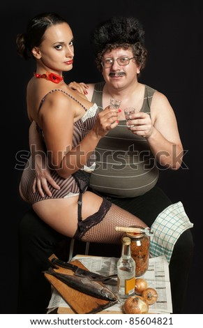 Russian man in fur hat and a sexy woman sitting on his lap and drinking vodka