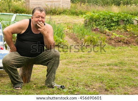 Russian man smokes in the village