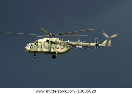 Russian military transport helicopter, sunlit against the dark cloud.