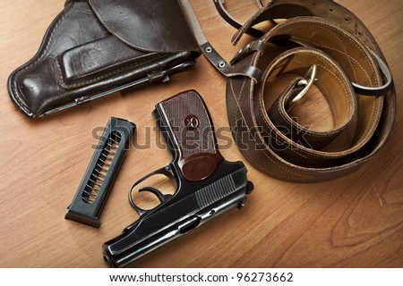 russian 9mm handgun PM (Makarov) on the table with holster, belt and empty pistol holder - stock photo