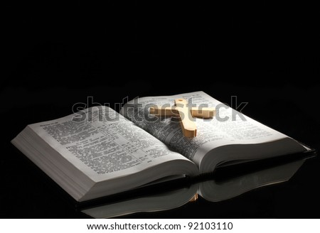 Russian open holy bible with wooden cross on black backround - stock photo