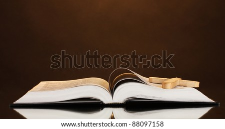 Russian open holy bible with wooden cross on brown backround - stock photo