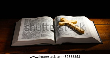 Russian open holy bible with wooden cross on table - stock photo