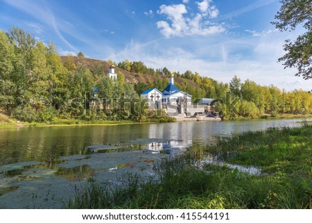 Russian Orthodox Church on the shore of a pond in autumn
