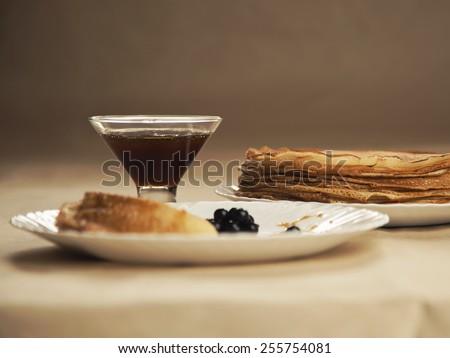 Russian pancakes with honey on table. Russian cuisine. Taste pancake. Black currant on white plate with pancakes.Blini. Maslenitsa. Pancake week. Butter Week. Cheesefare Week - stock photo