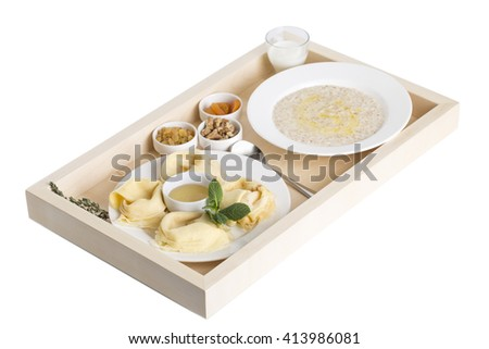 Russian pancakes with oatmeal and dried fruits on a wooden tray. Isolated on a white background. - stock photo