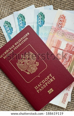 Russian passport with money on burlap background