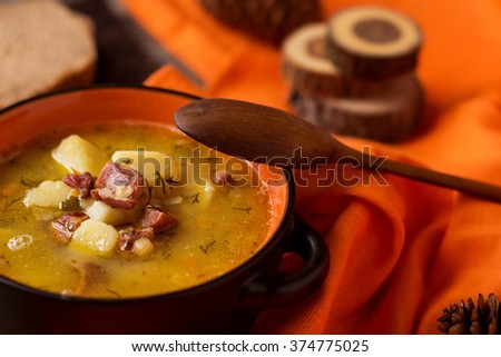 Russian peas soup with meat on orange and wooden background - stock photo