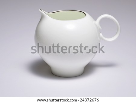 Russian porcelain milk jug with a golden rim - stock photo