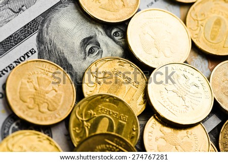 russian roubles coins on banknotes of dollars and  - stock photo