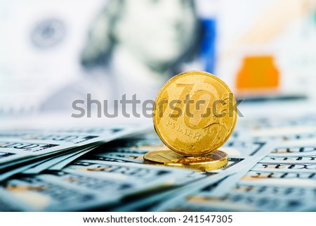 russian roubles coins on banknotes of us dollars  - stock photo