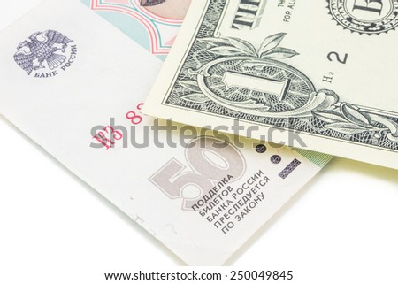 russian ruble and american dollar banknotes laying on white background - stock photo