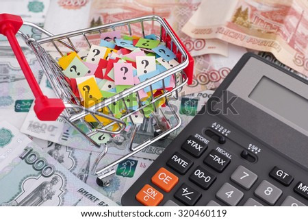 Russian ruble banknotes, shopping cart with question marks and calculator. Close up.