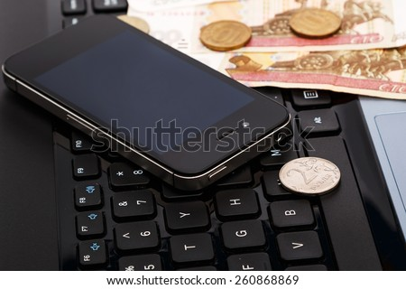 Russian rubles and smartphone over laptop keyboard - stock photo