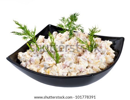Russian salad in a black plate on a white background - stock photo