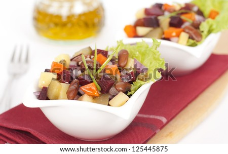 Russian salad vinaigrette served in two small plates on a dark red fabric - stock photo