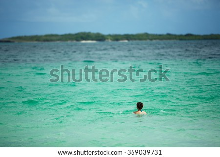 Russian skinny girl in a bathing suit bathes in a turquoise lagoon of a tropical Caribbean island in the Atlantic Ocean near the paradise of white sand beach - stock photo