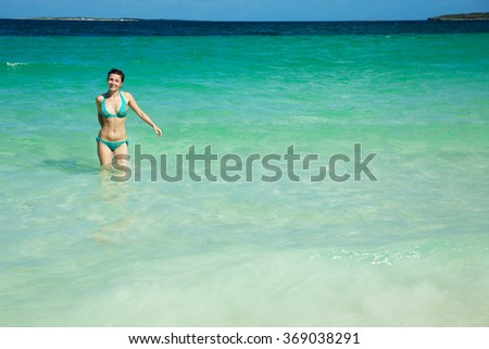 Russian skinny girl in a bathing suit relaxes on a paradise beach with white sand