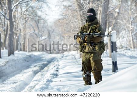 Russian soldier in winter uniform with the Kalashnikov machine gun on the forest background. - stock photo