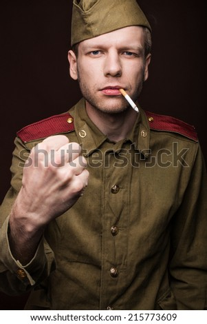 Russian soldier smoking cigarette and threaten with a fist. Studio portrait isolated on brown background   - stock photo