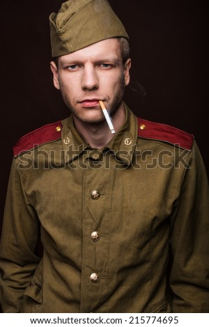 Russian soldier smoking cigarette. Studio portrait isolated on brown background - stock photo