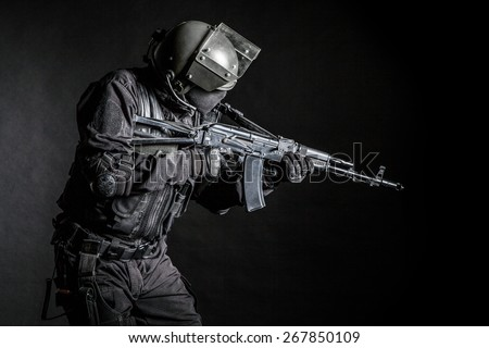 Russian special forces operator in black uniform and bulletproof helmet