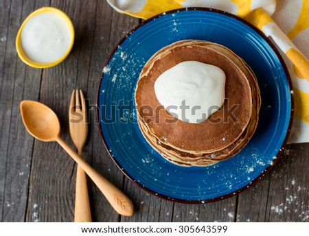 Russian style freshly baked pancakes with sour-cream - stock photo