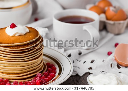 Russian style pancakes with redcurrants and tea on vintage wooden background - stock photo