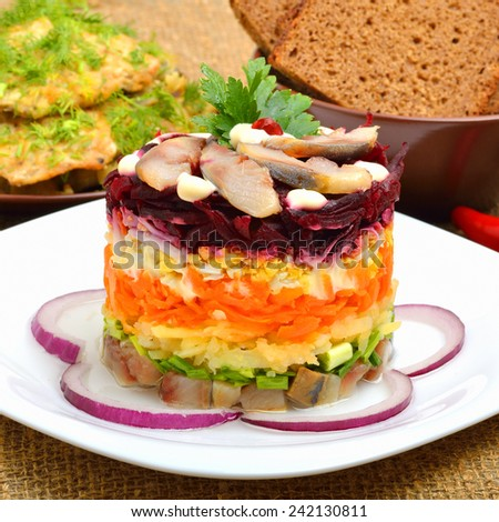 Russian traditional herring salad with beetroot, carrot, eggs on white pllate. Bread and cutlets - stock photo