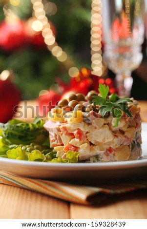 Russian traditional salad Olivier, on color napkin, on wooden  table, on bright background