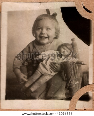 Russian vintage photograph, beginning of XX century. Laughing girl with a doll - stock photo