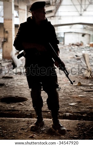 Russian warrior with Kalashnikov machine gun on the ruined building background.