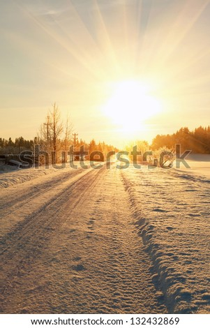 russian winter road and trees in snow blue sky and sun at sunset - stock photo