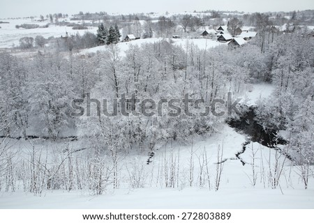 Russian winter. Snow-covered landscape with the village of Kruppsk near the Izborsk Fortress near Pskov, Russia. - stock photo