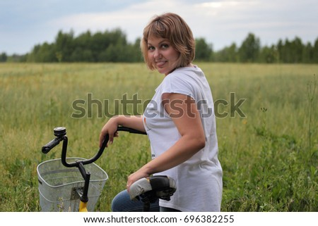 Russian woman in a wheat field. Walking on a bike in the summer.