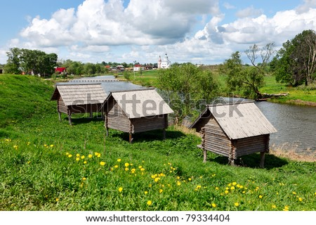 "Russian wooden huts (izba) on ""chicken legs"" at a Kamenka river bank in ancient russian town Suzdal."