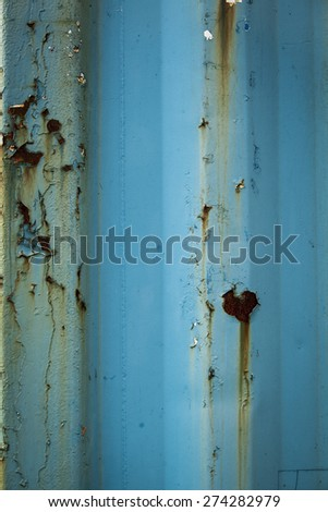 Rust and paint peel on a blue corrugated shipping container