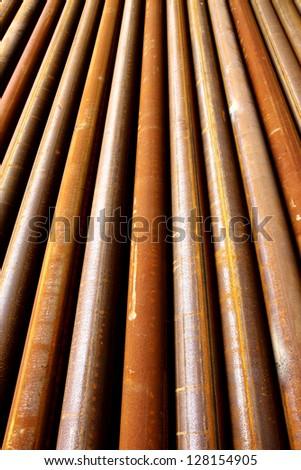 Rust steel pipes arrangement on the rack - stock photo