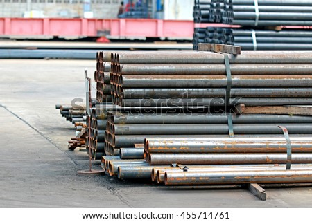 Rust steel pipes bunch on the rack in warehouse - stock photo