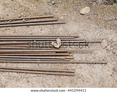 Rust steel rods & bar for construction on soil with dry leaves. Construction steel round bar. Abstract metal texture pattern of rusty. - stock photo