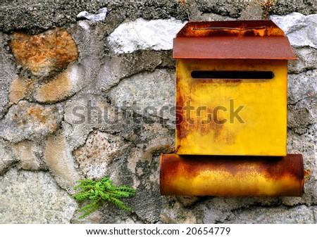 rust yellow mailbox on stone wall - stock photo