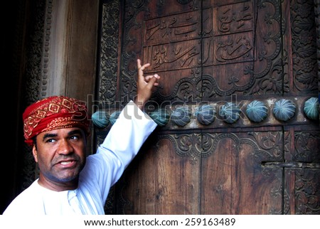 RUSTAQ, OMAN - DEC 23 2007:Omani tour guide explain the meaning of Arab words on the gate of Al Hazm Fort.Arabic is a Semitic language, date back to AD 512-568 closely related to Aramaic and Hebrew. - stock photo