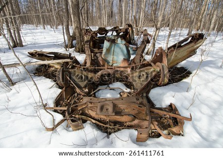 rusted car chassis resembling a dragon skull in the snow, upside down - stock photo