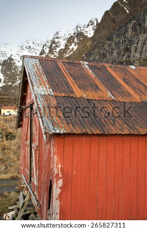 rusted corrugated iron roof of traditional fishing cabin against mountain backdrop, Lofoten, Norway - stock photo
