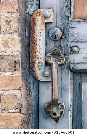 Rusted door handle and keyhole against brick wall - stock photo