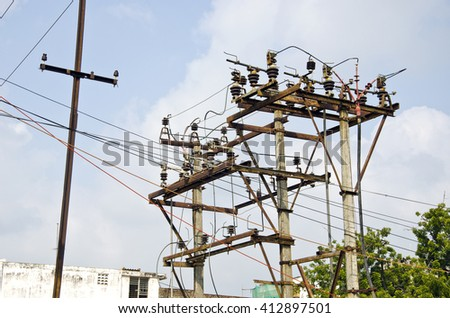 rusted electricity poles with many wires in urban area, India - stock photo