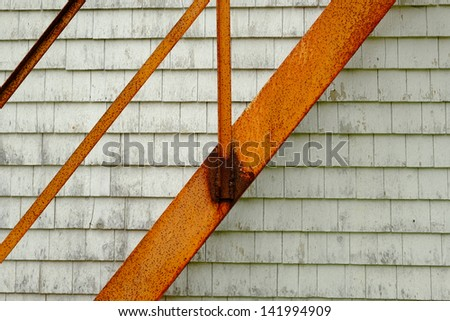 Rusted iron fire escape ladder on the side of clapboard building for safety