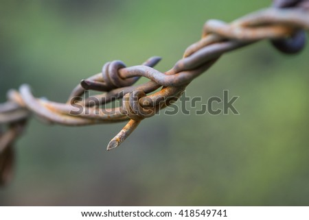 Rusted jagged tip of barbed wire on metal fence line. - stock photo