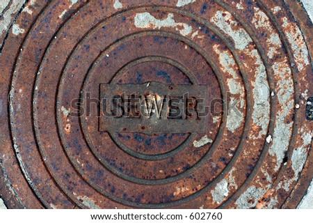Rusted manhole cover. - stock photo